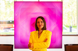 """© Licensed to London News Pictures. 19/05/2021. LONDON, UK. British abstract artist Nat Bowen' poses with her work 'Pink Diamond', 2021. Preview of """"Chromadelic"""", Nat Bowen's solo exhibition at 45 Park Lane in Mayfair. The artist uses the study of Chromology, the psychology behind colour, taking influences from the colours and shapes of the 60s and 70s, to layer resin pigmented with bright neon colours against rare natural pigments.  The highlight is the 'Pink Diamond' with natural rose petal pigment and genuine pink diamond dust set within 69 layers of resin.  Her show runs until 28 June 2021.  Photo credit: Stephen Chung/LNP"""