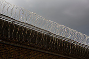 Razor wire fence attached to a large brick wall protecting the perimeter wall of HMP Pentonville, London, UK.  HM Prison Pentonville is an English Category B men's prison, operated by Her Majesty's Prison Service. Pentonville Prison is located on  Caledonian Road in the Barnsbury area of the London Borough of Islington, north London, United Kingdom. (Photo by Andy Aitchison)