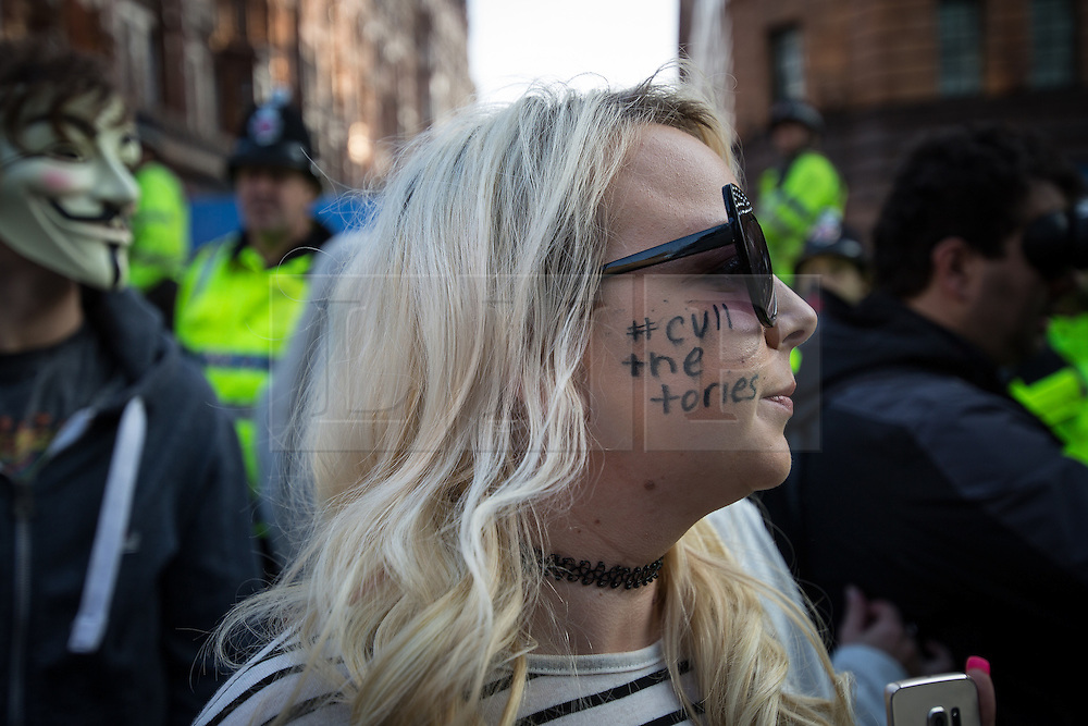 """© Licensed to London News Pictures . 04/10/2015 . Manchester , UK .  Woman with """" Cull the Tories """" written on her cheek . A demonstration against the Conservative government , organised by The People's Assembly , at Castlefield Bowl in Manchester , during the first day of the Conservative Party Conference in Manchester . Photo credit: Joel Goodman/LNP"""