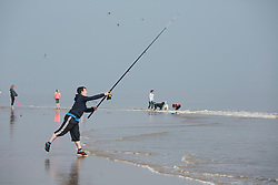 © Licensed to London News Pictures. 10/4/2015. Skegness, Lincolnshire, UK.<br /> People enjoying the warmest day of the year so far in the holiday resort of Skegness. Pictured, fishing for sea bass on the shore line. Photo credit : Dave Warren/LNP