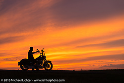 Tony Knight of Peoria, AZ takes in the sunset along highway 79 north of Sturgis and on the way to the Broken Spoke Saloon during the 75th Annual Sturgis Black Hills Motorcycle Rally.  SD, USA.  August 7, 2015.  Photography ©2015 Michael Lichter.