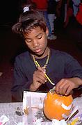 Pumpkin decorator age 10 at Youth Express Halloween party.  St Paul  Minnesota USA