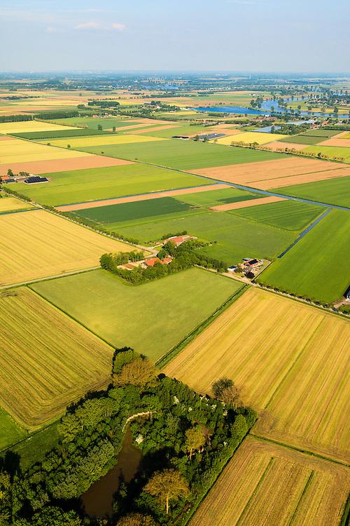 Nederland,  Land van Maas en Waal, Gelderland, 27-05-2013; West Maas en Waal, oorspronkelijk een gebied van komgronden (laag gelegen en nat gebied), versnipperd en slecht ontsloten.Onder in beeld een van de oorspronkelijke eendenkooien, boven in beeld de Maas. Grootschalige ruilverkaveling in combinatie met cultuurtechnische gebiedsverbetering is in de jaren vijftig (jaren '50) van de vorige eeuws gecombineerd met voorlichting en scholing van de bewoners.<br /> The low and wet land between the rivers Maas and Waal, central Netherlands  has been developed in the fifties by large-scale land consolidation and education, development and training of the residents. One of the main roads along the farms.<br /> luchtfoto (toeslag op standard tarieven)<br /> aerial photo (additional fee required)<br /> copyright foto/photo Siebe Swart