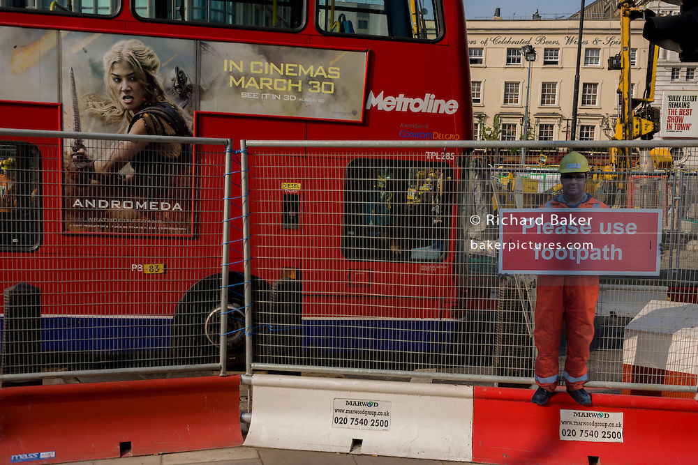 Passing red bus featuring Wrath of the Titans film ad and scaled human workman figure who warns pedestrians to stay on established footpath, and not wander into construction site roadways.