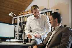 Two businessmen using digital tablet in an office and smiling, Bavaria, Germany