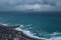 Distant mountain peaks become concealed in aproaching winter storm, Flakstadøy, Lofoten Islands, Norway