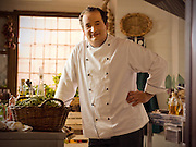 An Italian chef stands in his Tuscan kitchen, taking a break from cooking.