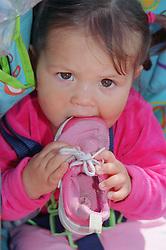 Portrait of baby girl sucking on shoe,