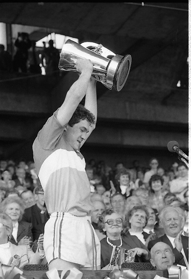All Ireland Hurling Finals.1986..07.09.1986..09.07.1986..7th September 1986..September,every year,is the highlight of the GAA calendar with The All Ireland Finals being held in both codes. The senior and minor finals in each code are both played for on the same day. Each finalist has battled through provinical and knock out stages to reach the final.It is widely regarded as the pinnacle of a players career to reach and win an All Ireland Championship..In this years hurling finals,Cork played Offaly in the minor championship and a much fancied Galway team took on Cork in the senior final. Both matches were well fought and close encounters...In the minor final Offaly ran out winners against Cork with a score of 3.12 (21) to 3.9 (18)...Image shows the victorious Offaly captain,Michael Hogan,holding the Irish Press Cup aloft in celebration after winning the All Ireland Minor Hurling Final.The Archbishop of Cashel, Dr T Morris is also pictured.