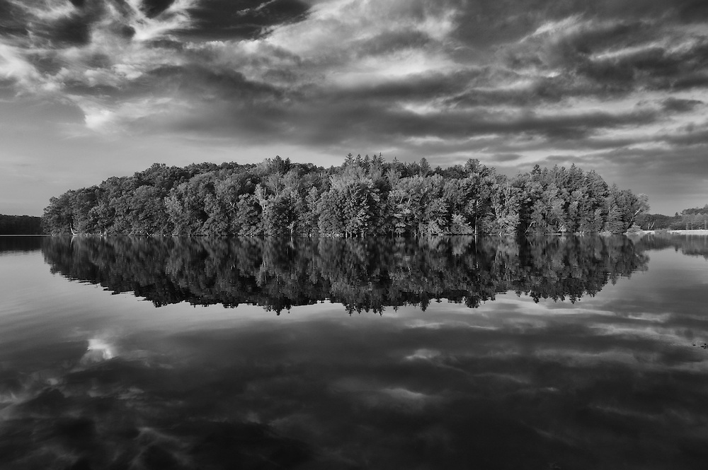 A forest is reflected in the still water of east branch reservoir in the early morning after sunrise near Brewster, New York.