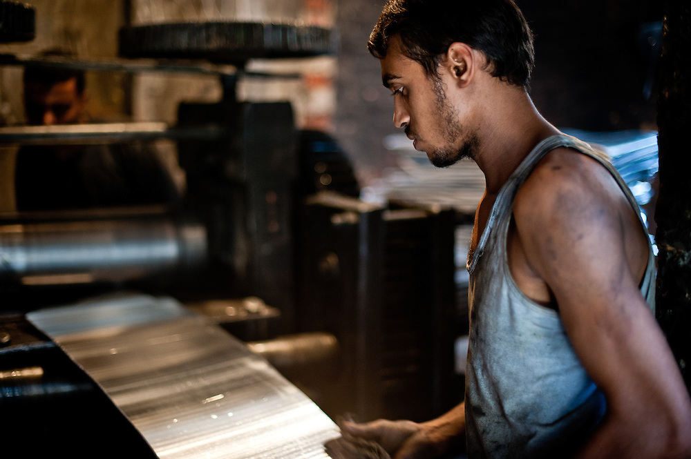 A man turns alumimum ingots into sheets of pressed aluminum in a workshop.