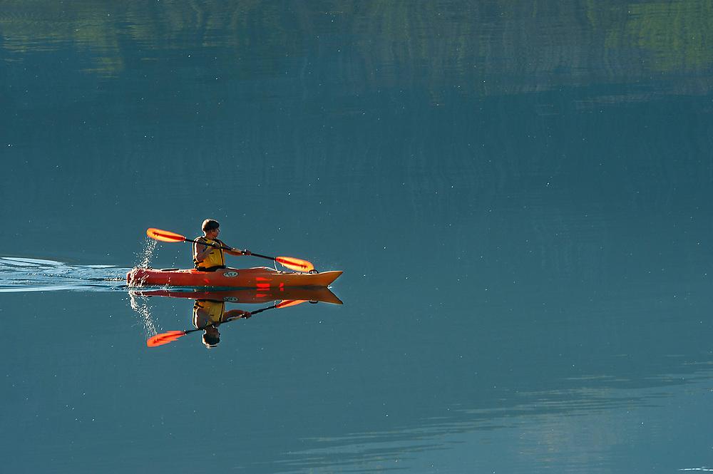 Solo kayaker glides across calm McDonald Lake in Glacier National Park, Montana