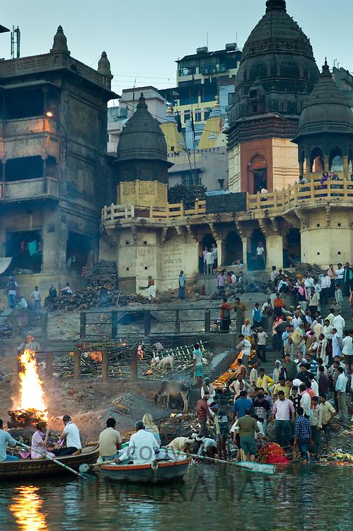 Tourists watch body bathed in River Ganges and traditional Hindu funeral pyre cremation, Manikarnika Ghat in Holy City of Varanasi, India