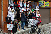 A father holding a child's buggy waits for his partner who has disappeared into a small clothing shop, on 17th September 2019, in Zakopane, Malopolska, Poland.