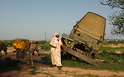 "Tiblits walks her donkey that she received from the womens union ""Hamade"",  past abandoned Ethiopian military vehicles as she heads to the watering hole."