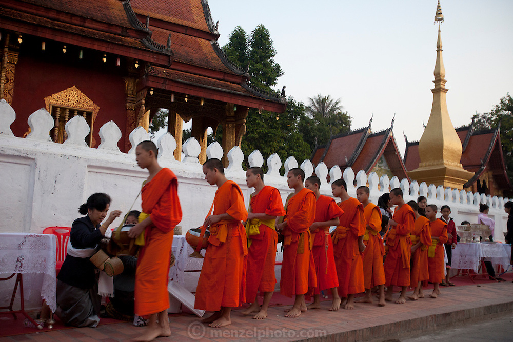 """Luang Prabang, Laos. Every morning at dawn, barefoot Buddhist monks and novices in orange robes walk down the streets collecting food alms from devout, kneeling Buddhists. They then return to their temples (also known as """"wats"""") and eat together. This procession is called Tak Bat, or Making Merit. At the Wat Sensoikharam."""