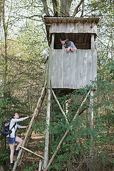 Young couple climbing on lookout tower in a forest, Bavaria, Germany