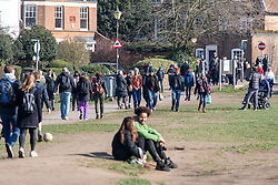 © Licensed to London News Pictures. 07/03/2021. London, UK. Members of the public enjoy a walk on Wimbledon Common in the sunshine this afternoon. From Monday, 8th March 2021 two friends will be allowed to socialise out side of their household for a coffee or picnic for the first time in months. England will begin Stage1 of the easing of lockdown tomorrow, with children returning to school, care homes allowing a visitor and friends being allowed to socialise out side of their household. However, pubs, shops and restaurants will still remain closed. Photo credit: Alex Lentati/LNP