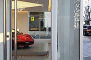 luxury car dealer showroom display with a red Ferrari sports car