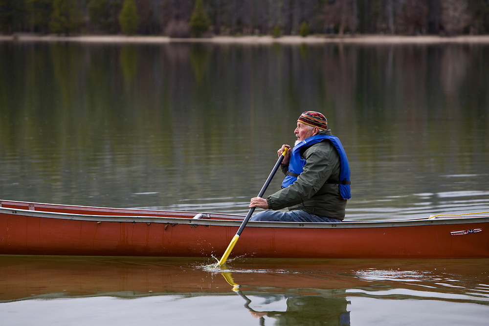 Jack floats across Redfish Lake in Central Idaho in his canoe.  Licensing and Open Edition Prints.