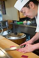Sushi chef Masatoshi Yoshino is cutting akami (red meat tuna) at his restaurant Yoshino Sushi Honten, Tokyo, Japan