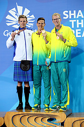 Scotland's Duncan Scott after winning silver in the Men's 200m Individual Medley Final with Australia's Mitch Larkin (centre, gold) and Clyde Lewis (right, bronze) at the Gold Coast Aquatic Centre during day six of the 2018 Commonwealth Games in the Gold Coast, Australia.