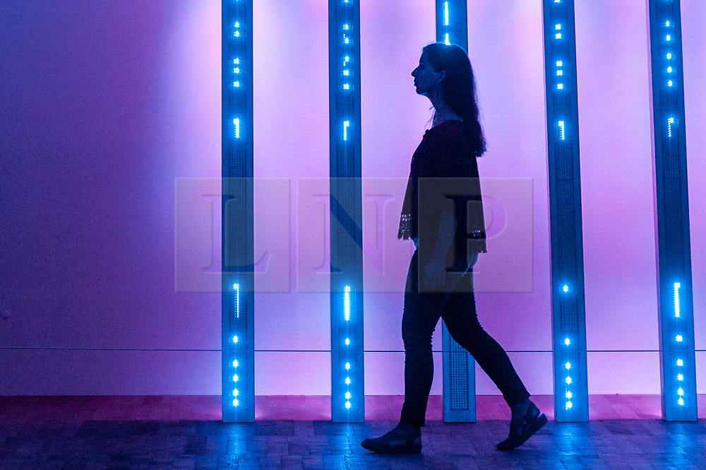 """© Licensed to London News Pictures. 20/07/2018. LONDON, UK. A staff member views """"BLUE PURPLE TILT"""", 2007, by Jenny Holzer at the preview of ARTIST ROOMS: Jenny Holzer at Tate Modern. The annual free display includes text-based installations and paintings by the American artist Jenny Holzer and runs 23 July to summer 2019.  Photo credit: Stephen Chung/LNP"""