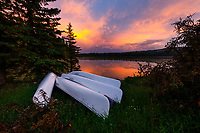 The beautiful glow of sunset over a raft of canoes on the shore of Westover Lake in the foothills west of Calgary.<br /> <br /> ©2017, Sean Phillips<br /> http://www.RiverwoodPhotography.com