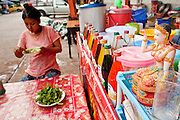 Oct. 6, 2009 -- SAMUT SAKHON, THAILAND: A Burmese woman eats at a roadside soup stand in front of shrimp processing plant in Samut Sakhon, Thailand. The Thai fishing industry is heavily reliant on Burmese and Cambodian migrants. Burmese migrants crew many of the fishing boats that sail out of Samut Sakhon and staff many of the fish processing plants in Samut Sakhon, about 45 miles south of Bangkok. Migrants pay as much $700 (US) each to be smuggled from the Burmese border to Samut Sakhon for jobs that pay less than $5.00 (US) per day.   Photo by Jack Kurtz / ZUMA Press