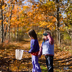 Two young girls (ages 4 and 6) on a woodland trail in Biddeford, Maine