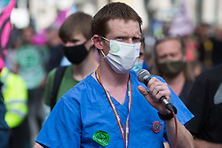 London, UK. 23rd August, 2021. A medical worker addresses environmental activists from Extinction Rebellion in the Covent Garden area during the first day of Impossible Rebellion protests. Extinction Rebellion are calling on the UK government to cease all new fossil fuel investment with immediate effect. Credit: Mark Kerrison/Alamy Live News