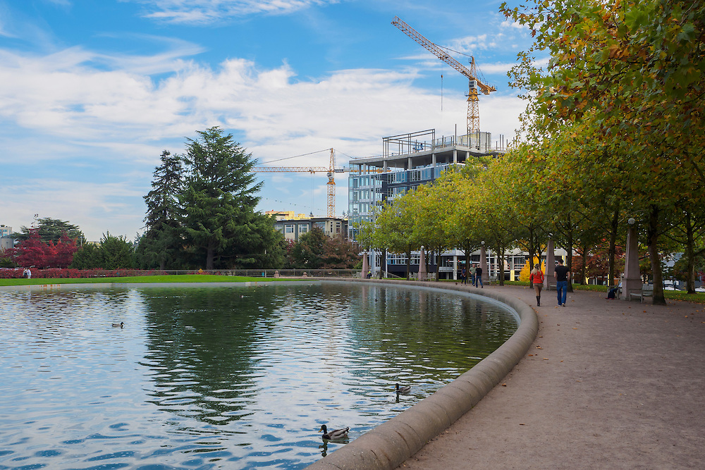 North America, United States, Washington, Bellevue. People strolling around the pond at Downtown Park in the autumn.
