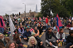 © Licensed to London News Pictures. 30/08/2021. London, UK. Protesters block TOWER BRIDGE taking part in EXTINCTION REBELLION'S THE IMPOSSIBLE REBELLION demonstration in the London Bridge area. Photo credit: Ray Tang/LNP
