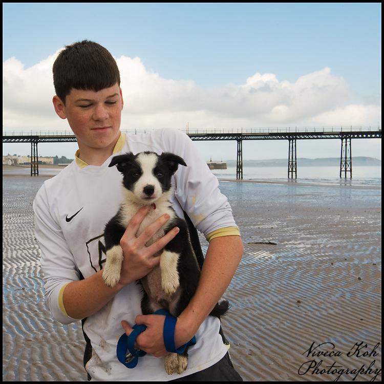 Boy holding a puppy on the beach, Ramsey, Isle of Man