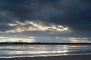 Sun rays through cloudy skyscene - dark clouds and Norfolk coastal scene at Titchwell, North Norfolk, England, UK