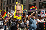 """New York, NY - 25 June 2017. New York City Heritage of Pride March filled Fifth Avenue for hours with groups from the LGBT community and it's supporters. A large contingent of marchers from Rise and Resist, many of whom were carrying signs, the largest of which here has a large photo of White House Press Secretary Sean Spicer, with the banner """"Sean Spicer / Queer Basher."""" superimposed over his mouth."""