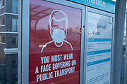 Public transport signs to wear a face covering or face mask while travelling on Docklands Light Railway or DLR trains on the day that it was announced that the Coronavirus lockdown measures are set to ease even further and the quiet city starts coming to an end, on 23rd June 2020 in London, England, United Kingdom. As of today the government has relaxed its lockdown rules, and is allowing some non-essential shops to open with individual shops setting up social distancing queueing systems.