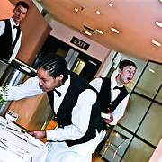 Male waiter placing glass on table with two waiters in the background.