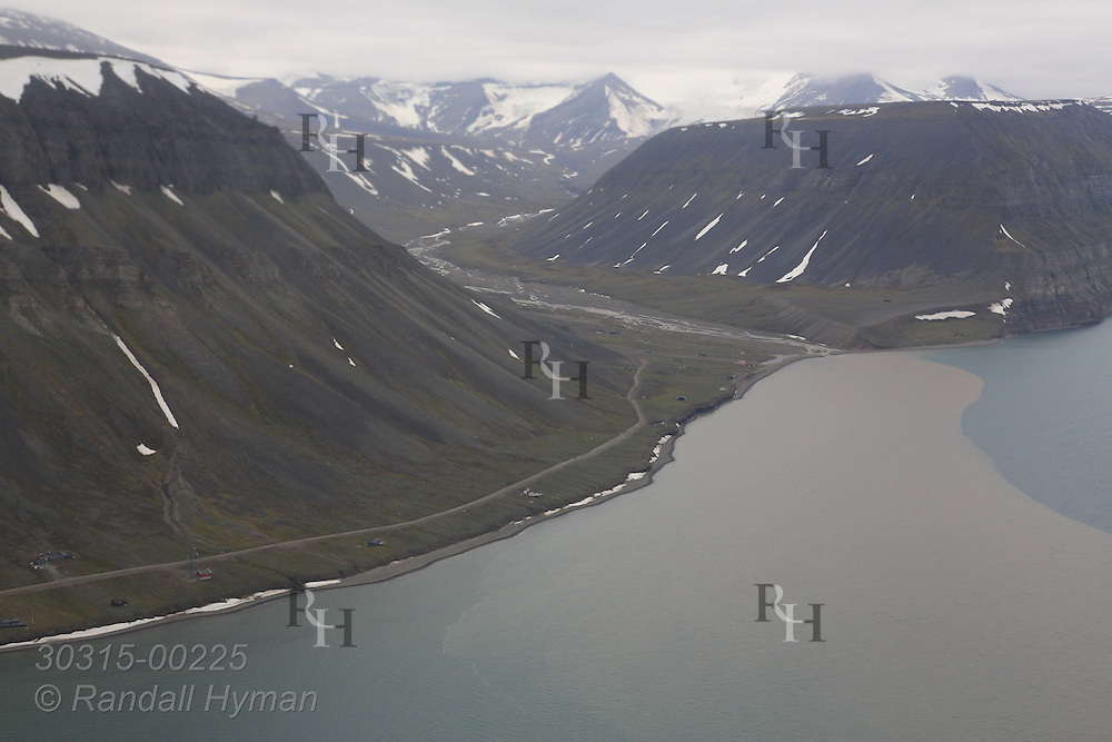 Aerial view in July of Isfjorden coast southwest of Longyearbyen with striking contrast between ocean water and silty freshwater from rivers of Bjorndalen in July; Spitsbergen island, Svalbard, Norway.