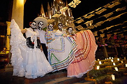 """North America, Mexico, San Miguel de Allende, teenagers in traditional costumes for Day of the Dead parade stand in front of La Parroquia de San Miguel Church, with its negothic facade floodlit at night, and streamers of tissue paper flags, known as """"Papel Picado."""""""