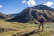 Day 4 of 10: A trekker pauses in the pastures of green Tuctubamba Valley in the Cordillera Blanca, Andes Mountains, Peru, South America. Trek 10 days around Alpamayo in Huascaran National Park (UNESCO World Heritage Site).