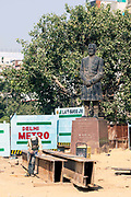 A worker spot welds metal by the Metro construction at Kashmere Gate next to a statue of Asif Ali, Delhi, India