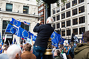A man climbs into a lamppost to photograph the People's Vote march