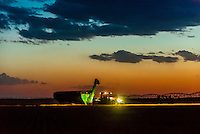Farmers harvesting wheat late in the evening, Schields & Sons Farming, Goodland, Kansas USA.