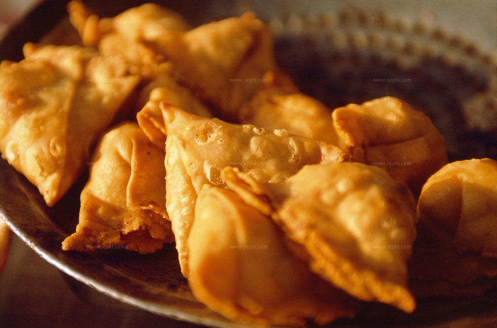 Samosa can most probably have the title of 'king of street food' as it is vitualy everywhere. .It generally consists of a fried triangular- or tetrahedron-shaped pastry shell with a savory potato, onion, fresh coriander, Paneer (cottage cheese) and pea stuffing, and is often eaten with chutney, such as mint, coriander or tamarind.