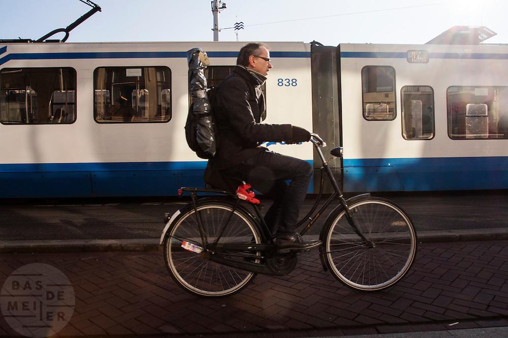 In Amsterdam fietst een man met een gitaar op zijn rug over het Damrak.<br /> <br /> In Amsterdam a man cycles with a guitar on his back at the Damrak.
