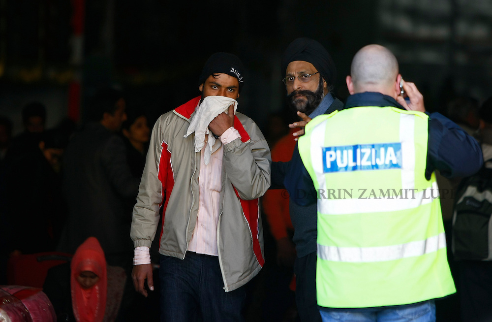 An Indian man (L) is assisted by an embassy official to disembark from the ferry MV Red Star One after arriving at Valletta's Grand Harbour March 6, 2011.  The Indian-chartered ferry arrived in Malta from Misurata in Libya on Sunday morning carrying 301 evacuees, mostly Indians but also including Filipino, British and Bangladeshi nationals...REUTERS/Darrin Zammit Lupi (MALTA)