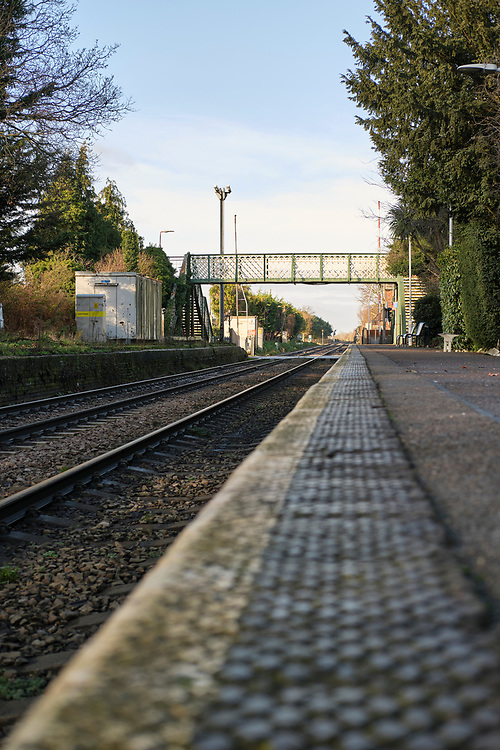 Low level view along the platform at Trimley station along the line away fro Felixstowe. The station footbridge & level crossing is visible & the second platform which is no longer in use.<br /> <br /> Photo by Jonathan J Fussell, COPYRIGHT 2020