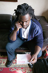 Man reading a utility bill in his home,