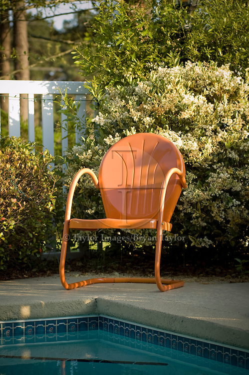 An orange metal chair, in front of a flowering bush, overlooks the still summer water of a backyard swimming pool.